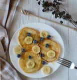 Frukostera pannkakor med bananen, blåbär och honung arkivbilder