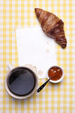 Frukostera platsen med kaffe, gifflet, driftstopp och tomt papper Arkivfoton