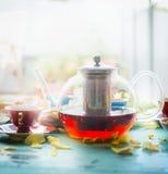 Frukostera platsen med krukan av te, koppen och kakan på fönstret Royaltyfria Bilder