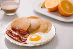 Frukostera plattan med pannkakor, ägg, bacon och frukt Arkivfoto