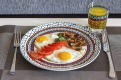 Frukostera stekte ägg med grönsaker och orange fruktsaft Fotografering för Bildbyråer