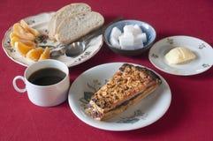 Frukostera uppsättningen med kakan, kaffe, brödsmör och apelsinen royaltyfria foton