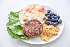 Frukostera uppsättningen, nötkött, omelettet, blåbäret, grönsaken, tunn pannkaka arkivbild