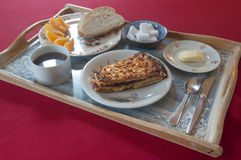 Frukostera uppsättningen på ett dekorerat magasin med kakan, kaffe, bröd, smör och apelsinen arkivfoton