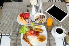 Frukostera uppsättningen på tabellen med pannkakor, bacon, ägg och kaffe royaltyfri fotografi