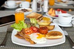 Frukostera uppsättningen på tabellen med pannkakor, bacon royaltyfri bild