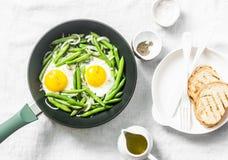 Frukostkastrull Stekte ägg med haricot vert Sunt ätabegrepp på vit bakgrund, bästa sikt royaltyfri foto