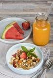 Frukostmyslit med mjölkar eller yoghurten, muttrar och jordgubbar, orange fruktsaft och vattenmelon royaltyfri foto