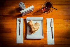 Frukostpannkakor med fyllning i en härlig vit platta och ett exponeringsglas av turkiskt te på en härlig trätabell royaltyfria bilder