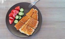 Frukostplatta på trätabellen Stekt rostat brödbröd och tomatgurka för frukost royaltyfri bild