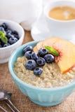 Frukostquinoahavregröt med nya frukter arkivfoton