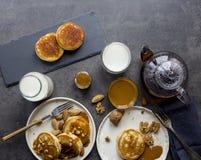 Frukostsammansättning med pannkakor, mjölkar och te på svart bakgrund arkivfoto