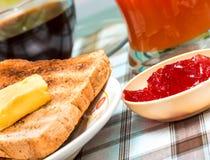 Frukostsmörrostat bröd föreställer den fruktsylter och drycken royaltyfria foton