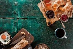 Frukostspridning med kaffe, bröd och sylter arkivfoto