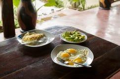 Frukosttabell med platta stekte ägg, förvanskade ägg och avocad arkivbilder