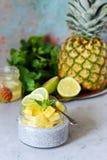 Frukosttabellen med Chia fruktsmoothies bowlar med stycken av ananas-, limefrukt-, honung- och mintkaramellsidor sund mat Top bes Royaltyfria Bilder