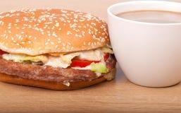 Frukostuppsättning: kaffe hamburgare på träbakgrund. Royaltyfri Bild