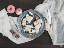 Frukostuppsättning på det mörka träskrivbordet: äpple- och kanelpannkakor Arkivfoto