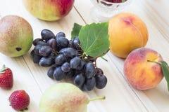 Frukt av nedgången av hösten äpplen, päron, blåa druvor, persikor och juicе Bakgrund frukt med det gröna bladet Arkivbilder