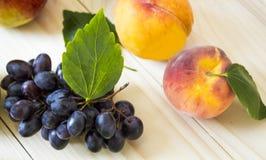 Frukt av nedgången av hösten äpplen, päron, blåa druvor, persikor och juicе Bakgrund frukt med det gröna bladet Royaltyfri Fotografi