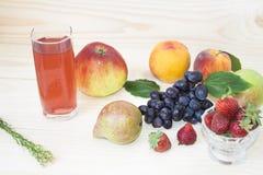 Frukt av nedgången av hösten äpplen, päron, blåa druvor, persikor och juicе Bakgrund frukt med det gröna bladet Royaltyfri Bild