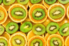 Frukt- bakgrundsuppsättning av skivor av orange frukt och kiwin Royaltyfria Bilder