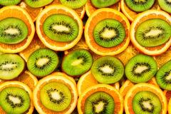 Frukt- bakgrundsuppsättning av skivor av orange frukt och kiwin Många skivor av kiwi och orange frukt, Fotografering för Bildbyråer