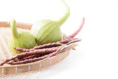 Frukt för flaskkalebass och lilacowpea i den isolerade korgen Arkivbilder