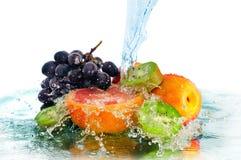 Frukt i en spray av vatten arkivfoton