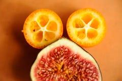 Frukt i ett snitt på tabellen Ljus saftig frukt, fikonträd, kumquat Sol- lynne för sommar Royaltyfria Bilder