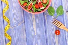 Frukt- och grönsaksallad, gaffel med det måttband-, bantning- och näringbegreppet, kopieringsutrymme för text royaltyfria foton