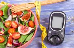 Frukt- och grönsaksallad, glukosmeter för mätningssockernivå och måttband, begrepp av sockersjuka arkivbilder