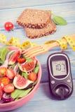 Frukt och grönsaksallad och glucometer med måttband, begrepp av sockersjuka, bantning och sund näring Arkivfoto