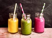 Frukt- och grönsakSmoothies i krus med sugrör royaltyfria bilder