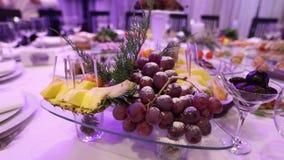 Frukt och mat på banketttabellen i restaurangen, stycken av ananas och grupper av druvor på banketttabellen lager videofilmer
