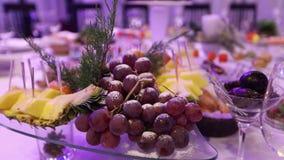 Frukt och mat på banketttabellen i restaurangen, stycken av ananas och grupper av druvor på banketttabellen arkivfilmer