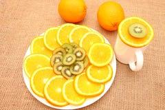 Frukt på en plattahand korrigerar skivan av apelsinen Arkivbild