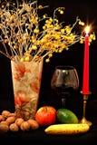 Fruktblandning, exponeringsglas av vin, röd stearinljus och vas av blommor på svart bakgrund Royaltyfria Foton