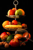 Fruktblandning i platta och exponeringsglas av vin på svart bakgrund Royaltyfri Foto