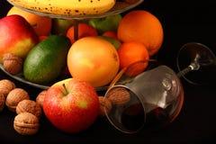 Fruktblandning i platta och exponeringsglas av vin på svart bakgrund Royaltyfri Fotografi