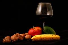 Fruktblandning och exponeringsglas av vin på svart bakgrund Arkivbilder