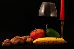 Fruktblandning, stearinljus och exponeringsglas av vin på svart bakgrund Royaltyfri Bild