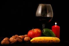 Fruktblandning, stearinljus och exponeringsglas av vin på svart bakgrund Royaltyfria Bilder