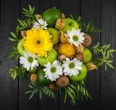 Fruktbukett med äpplen, gula blommor, kiwi och avokadot Royaltyfria Foton
