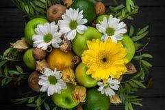 Fruktbukett med äpplen, gula blommor, kiwi och avokadot Royaltyfria Bilder
