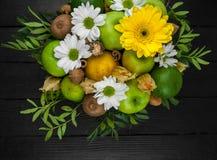 Fruktbukett med äpplen, gula blommor, kiwi och avokadot Arkivbilder