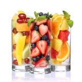 Fruktcoctailar som isoleras på vit. Nya stycken av frukt i exponeringsglas med mintkaramellen på överkanten. Arkivfoton
