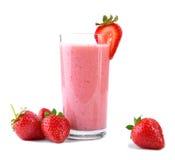 Fruktdrycken med jordgubbar och mjölkar Ett exponeringsglas som är fullt av nya och ljusa röda jordgubbar och organiskt, mjölkar  Arkivfoto