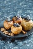 Fruktefterrätten bakade äpplen som var välfyllda med björnbäret, blåbär, kanel, muttrar, honung royaltyfri fotografi
