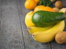 Frukten är gräsplan, den mogna avokadot, tre bananer och andra tropiska frukter på en lantlig tabell Arkivbilder